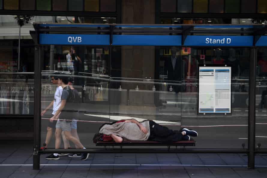 A man is seen sleeping in a bus shelter outside the Queen Victoria Building in Sydney.