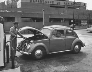 An attendant pumping gas for a customer driving a Beetle in 1954.