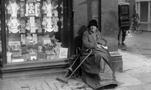 An elderly woman sits by a shop window full of adverts for cigarettes, 1935.