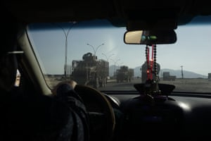The photograph is taken from inside a car. A tank can be seen through the car's windscreen.