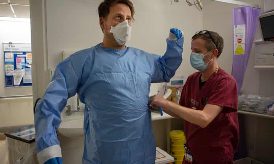 Dr Ben Lovell being helped into PPE before entering the secure part of the acute medicine unit.