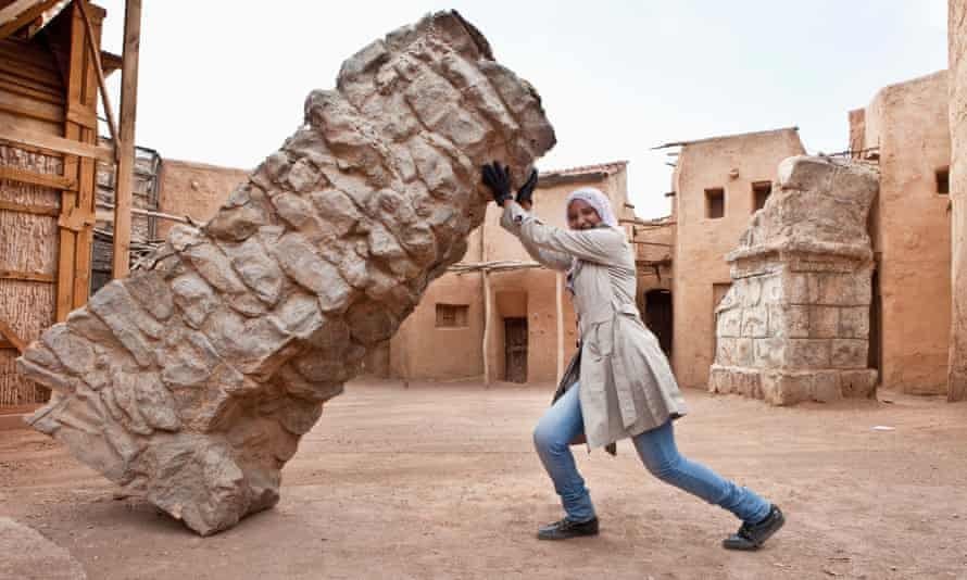 A tour guide poses with a prop at a film studios near Ouarzazate