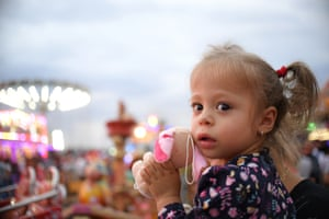 A girl holds a toy at a fair in Titu