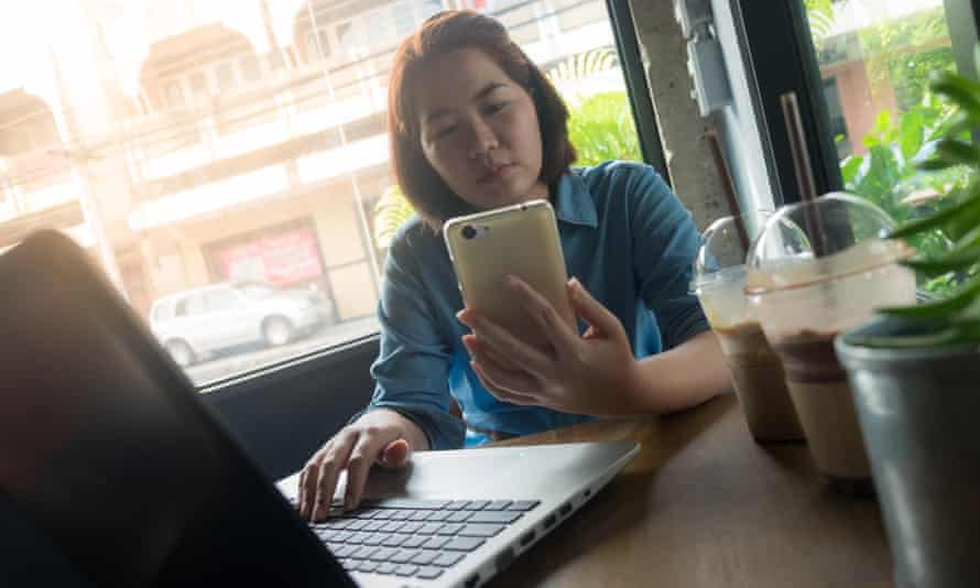 Woman using smartphone while working in coffee shop.