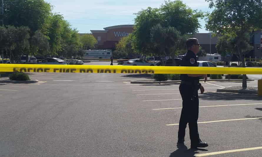 Chandler police spokesman Seth Tyler stands behind crime tape at the scene of a police-involved shooting at a Walmart store in Chandler, Arizona.