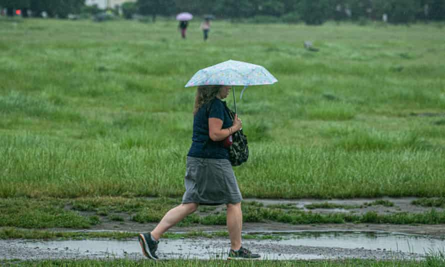 Woman walks on a wet, muddy path surrounded by grass