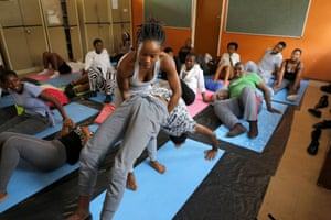Dipuo Smith helps a school student with the full wheel pose during a yoga class