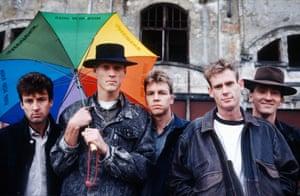 Portrait of Midnight Oil with Greenpeace 'Acid Rain' umbrella in 1988. L-R: Rob Hirst, Peter Garrett, Martin Rotsey, Bones Hillman, Jim Moginie.