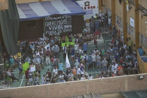 "Inmates hold a sign that reads in Spanish ""Right to life. We want to live but outside these walls,"" as they gather at a patio during the riot"