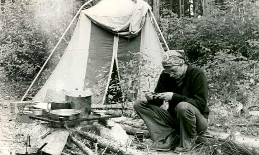 Annie Proulx, hair in a kerchief, sitting on a log in front of a tent and looking down
