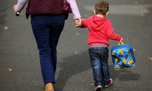 A child clutching a schoolbag holds hands with a parent.