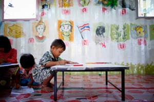 Three-year-old Paij draws a picture at the school