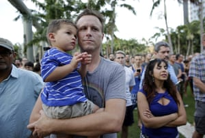 Miami Beach, Florida, US. Edwin Scharlau holds his son Joshua as a crowd prays for the victims of the Orlando attack