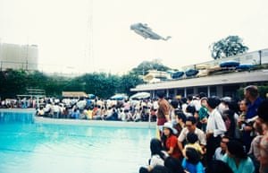Evacuees inside the US embassy surround the swimming pool as helicopter rescues stranded civilians trying to escape North Vietnamese troops about to capture Saigon.