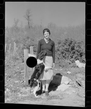 a young woman stands at the edge of wooded area, with a dog jumping up at her and a black circle beside them