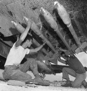 US Marines load five-inch rockets under the wing of a Corsair fighter during Battle of Okinawa