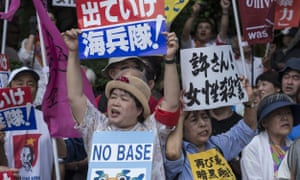 Protesters holding signs saying 'No base' in Okinawa, Japan