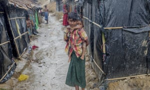 A Rohingya Muslim boy, who crossed over from Myanmar into Bangladesh, holds his brother outside his shelter as it rains in Balukhali refugee camp, Bangladesh.