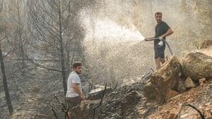 Men douse a fire in Mugla province, Turkey