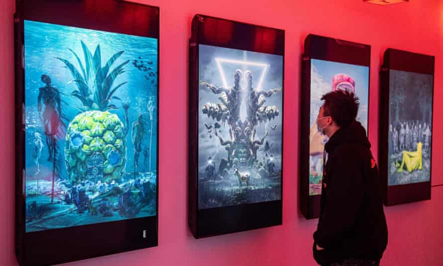 A man looks at digital paintings by US artist Beeple at a crypto art exhibition in Beijing titled Virtual Niche: Have You Ever Seen Memes in the Mirror?