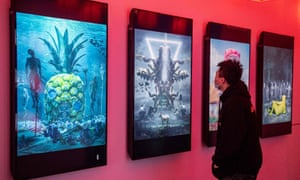 CHINA-ART-BLOCKCHAIN<br>A man looks at digital paintings by US artist Beeple at a crypto art exhibition entitled Virtual Niche: Have You Ever Seen Memes in the Mirror?, one of the world's first physical museum shows of blockchain art, ahead of its opening in Beijing on March 26, 2021. (Photo by NICOLAS ASFOURI / AFP) / RESTRICTED TO EDITORIAL USE - MANDATORY MENTION OF THE ARTIST UPON PUBLICATION - TO ILLUSTRATE THE EVENT AS SPECIFIED IN THE CAPTION (Photo by NICOLAS ASFOURI/AFP via Getty Images)