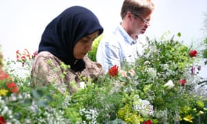 A white European man and an Asian woman tend to flowers