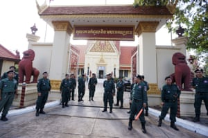 Police officers stand guard at the supreme court in Phnom Penh