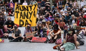 Protesters are seen during a vigil to mourn the death in police custody of Aboriginal woman Sherry Tilberoo hold a sign saying 'Aunty Tanya Day'