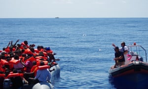 Migrant Offshore Aid Station (MOAS) staff throwing bottles of water from a dinghy to refugees in a rubber raft near Malta. The charity says it has said more than 10,000 lives during its first year in operation.