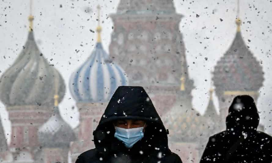 A man wearing a facemask in Red Square, Moscow, with the Saint Basil cathedral on the background
