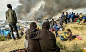 Children watch Calais refugee camp burn