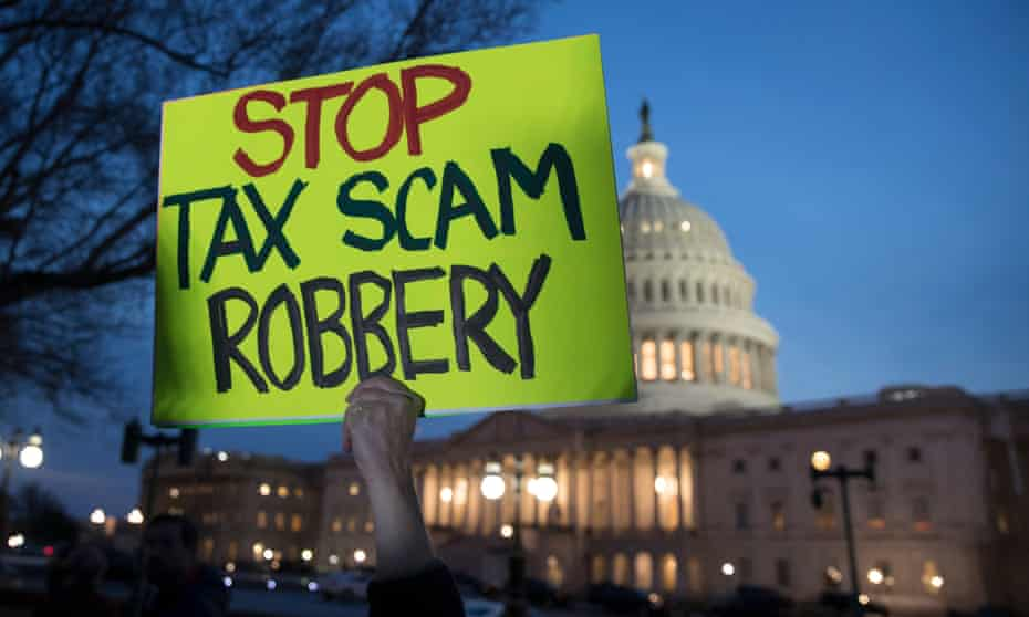 A person participating in a rally holds a sign in protest of a Republican-crafted tax cut plan, outside the US Capitol Building after sunset in Washington DC.