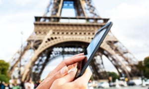 A woman uses a mobile phone in front of the Eiffel Tower
