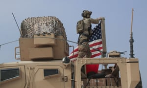 An American soldier mounts the US flag on a vehicle near the town of Tel Tamr in northern Syria.