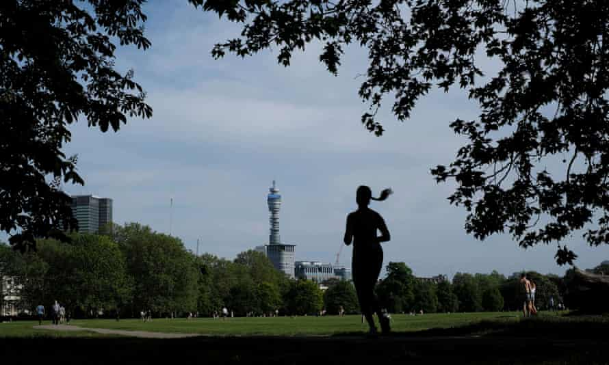 The silhouette of a jogging woman is seen in Regents Park, London.