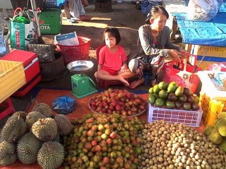 'Tran Thi Thanh Loan earns a few dollars a day by buying fruit from local orchards, which she sells in front of her parents' home.'
