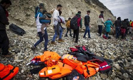 Syrian refugees walk past life vests after arriving on Mytilene beach, Lesbos, Greece