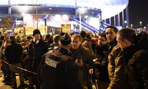 Football fans gather outside the Stade de France on Friday night after the stadium was evacuated due to the proximity of the terror attacks.