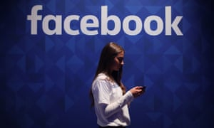 A woman using her phone under a Facebook logo.