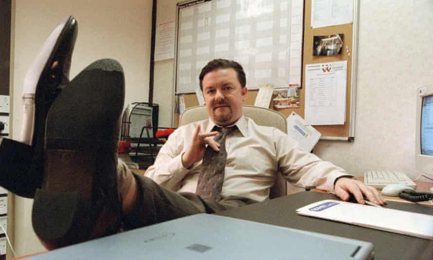 Ricky Gervais, his feet up on a desk, as David Brent in The Office.