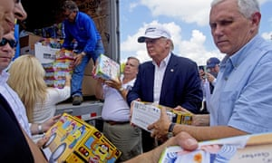 Republican presidential candidate Donald Trump and his running mate, Indiana Gov. Mike Pence, right, help to unload Play-Doh for flood victims during a tour of the flood damaged area in Gonzales, La., Friday, Aug. 19, 2016.