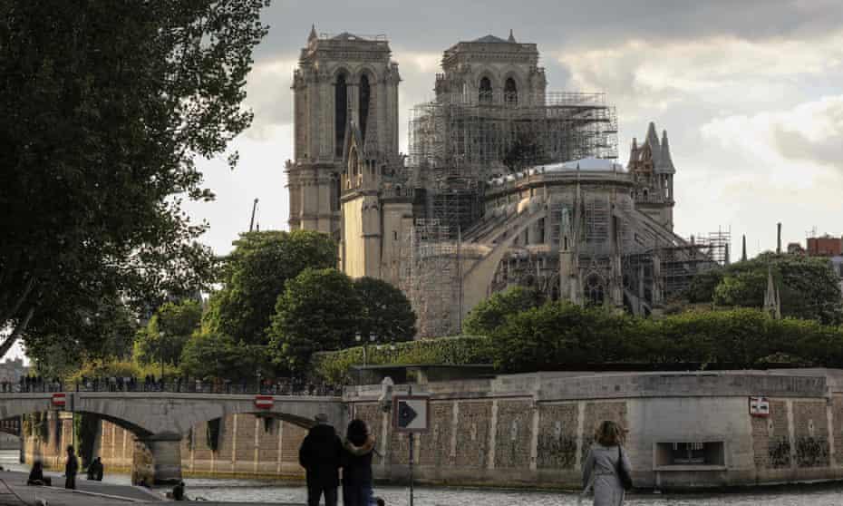 Pedestrians walking towards Notre Dame cathedral in Paris.