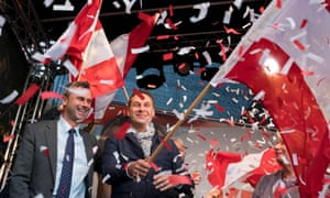 Norbert Hofer and the FPÖ chairman, Heinz-Christian Strache (right) wave flags on stage during Hofer's final election campaign rally at the Viktor Adler Markt in Vienna