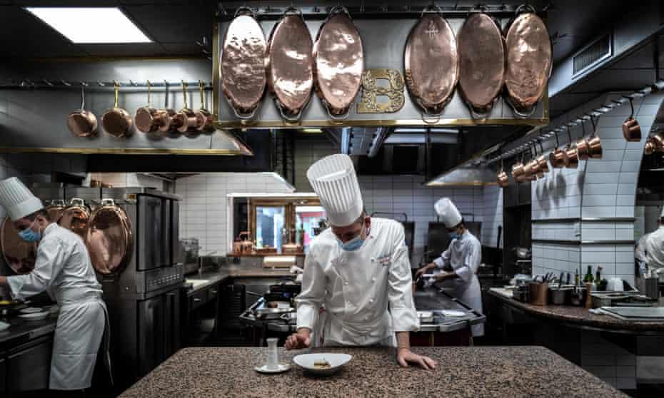 سرآشپز فرانسوی ژیل رینهارد (C) پاهای قورباغه را در رستوران پل بوکوسه آماده می کند