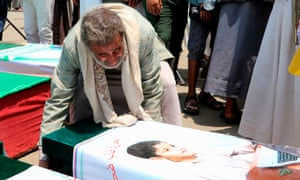 A Yemeni man mourns over a boy's casket during a mass funeral on Monday.