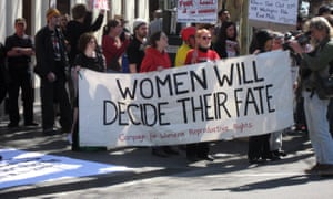 Pro-abortion campaigners hold a sign reading,