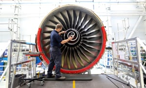 An employee fits the nose cone to a Trent 700 aircraft engine on the production line at the Rolls-Royce factory in Derby, UK