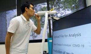 Un miembro del personal demuestra el uso del kit de prueba de alcoholímetro Breathonix en Singapur