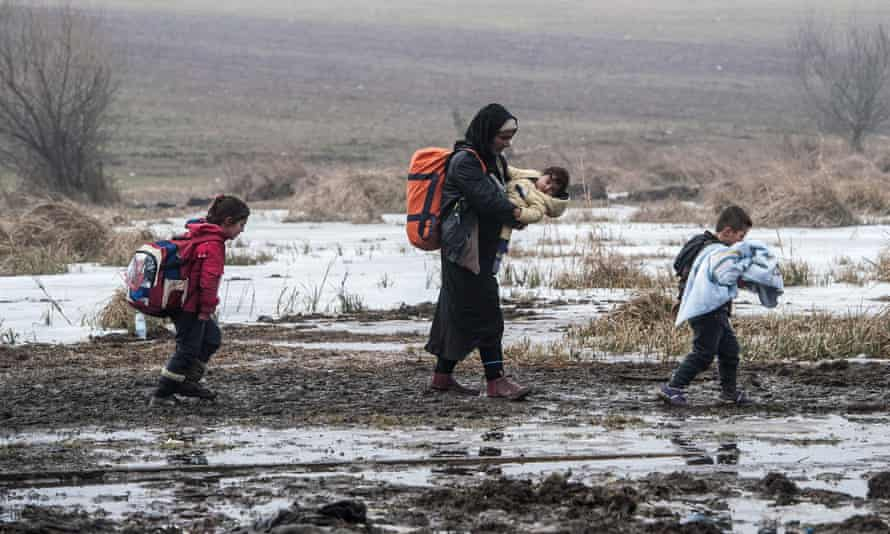Migrants and refugees walk after crossing the Macedonian border.
