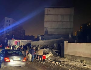 People standing next to a damaged building on the side of the road